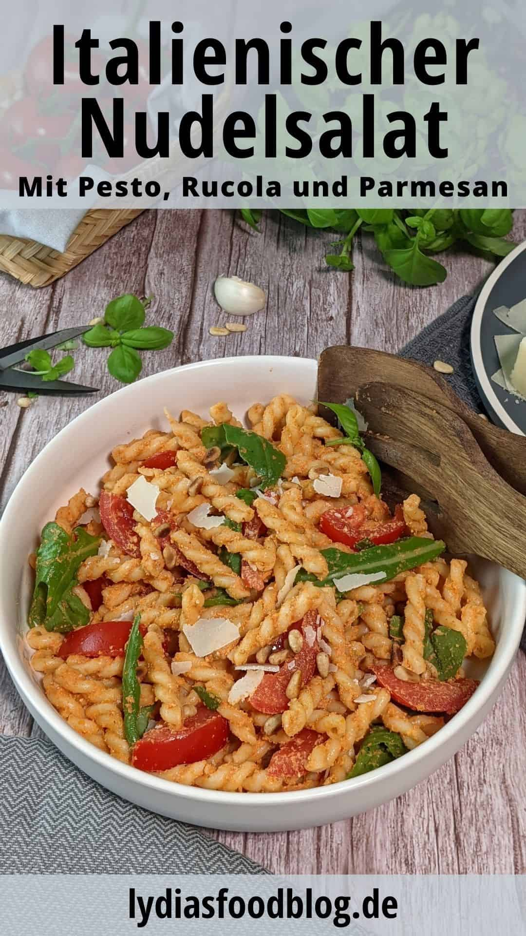 In einer weißen Schale ein italienischer Nudelsalat mit Tomate, Rucola und rotem Pesto.