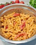 In einer Schale ein Nudelsalat mit Tomaten und rotem Pesto.