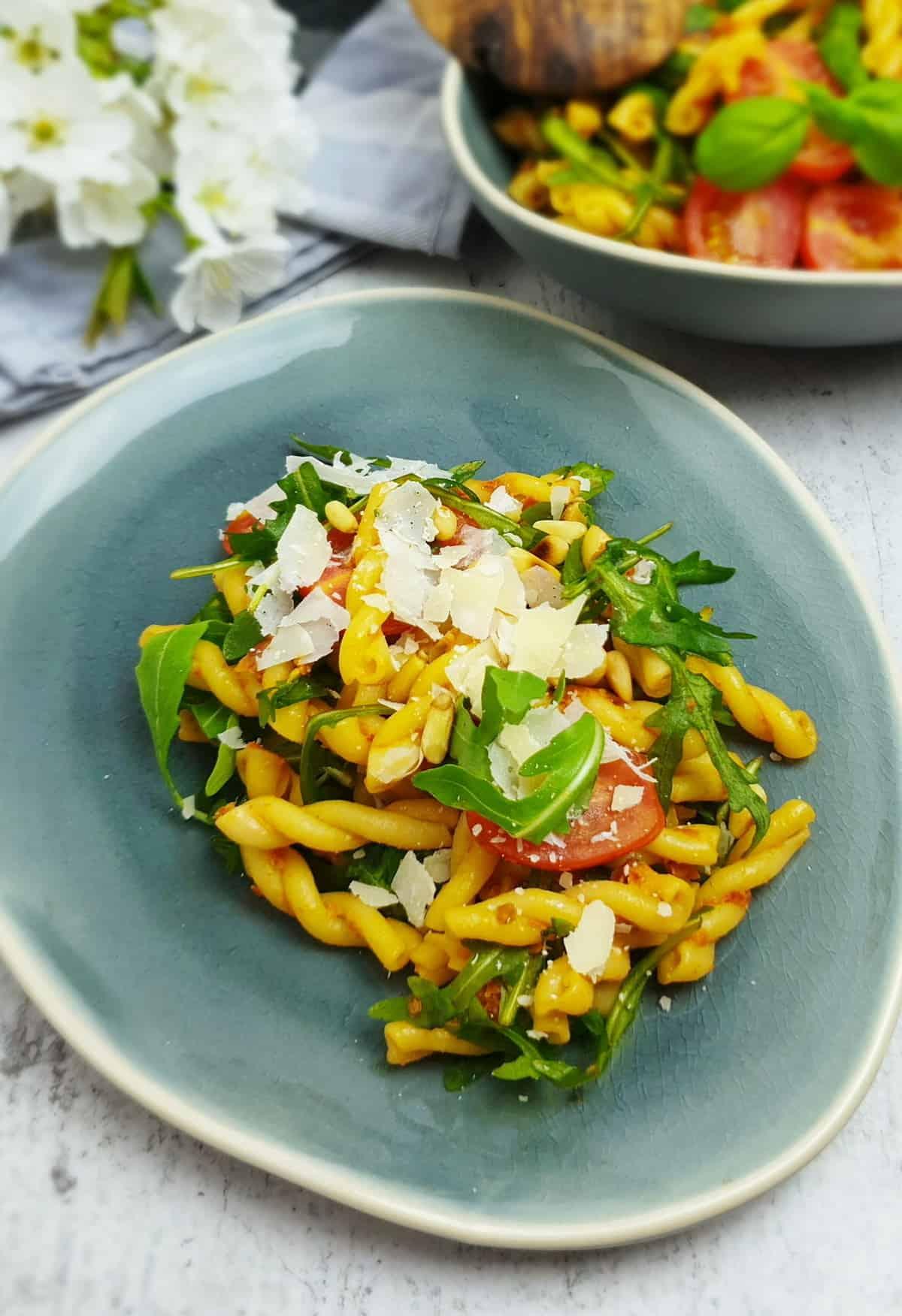 Auf einem blaugrauen Teller angerichtet ein italienischer Nudelsalat mit rotem Pesto, Tomaten, Rucola und Parmesan. Im Hintergrund Deko.
