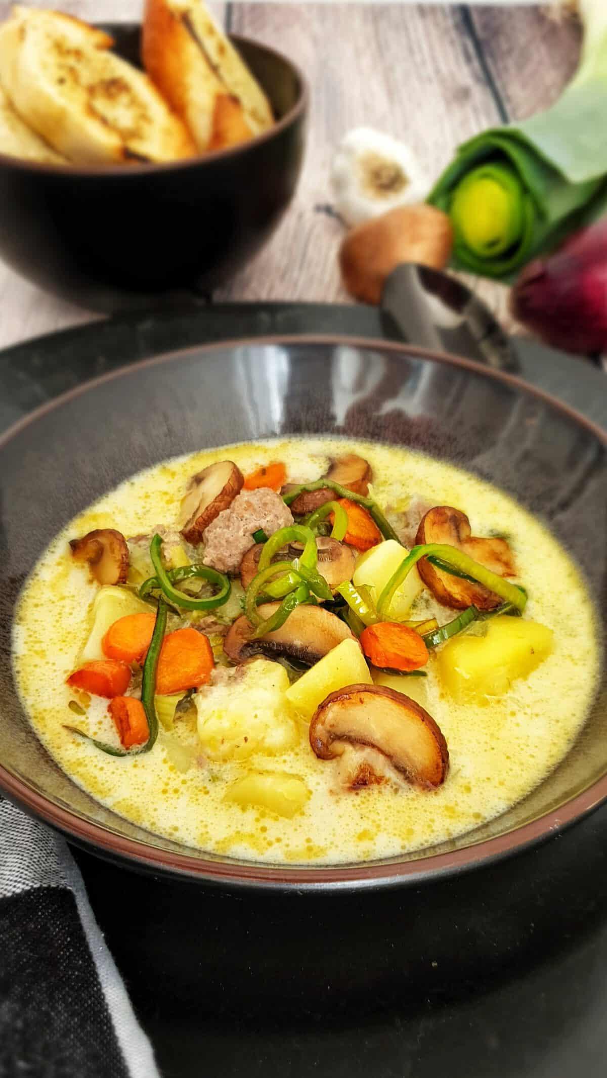 Käse-Lauch-Suppe mit Hackbällchen in einer braunen Suppenschale. Im Hintergrund Deko.
