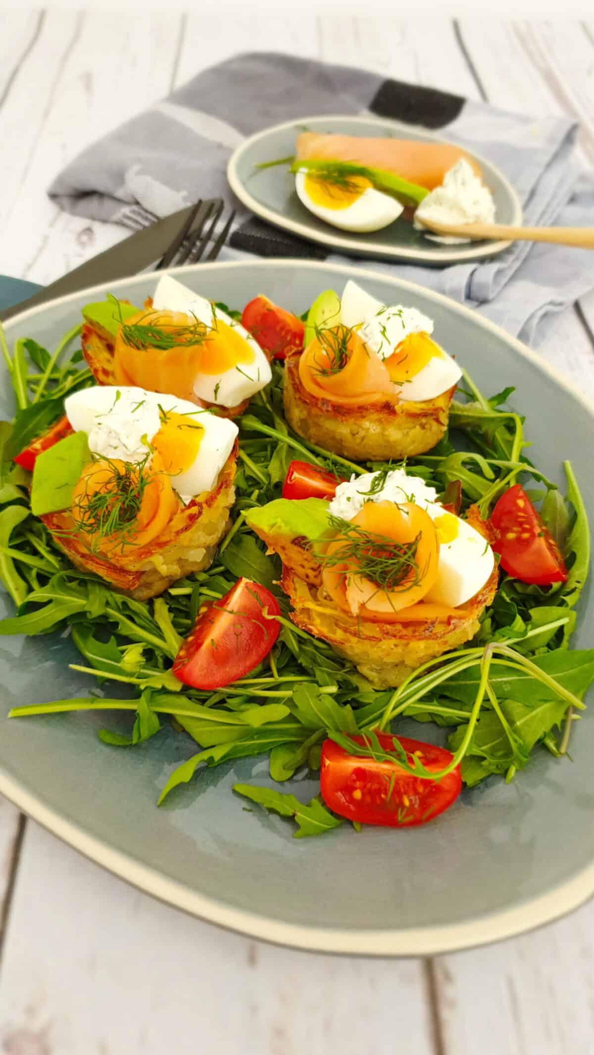 Kartoffelnester mit Lachs und Avocado angerichtet auf einem blauen Servierteller.