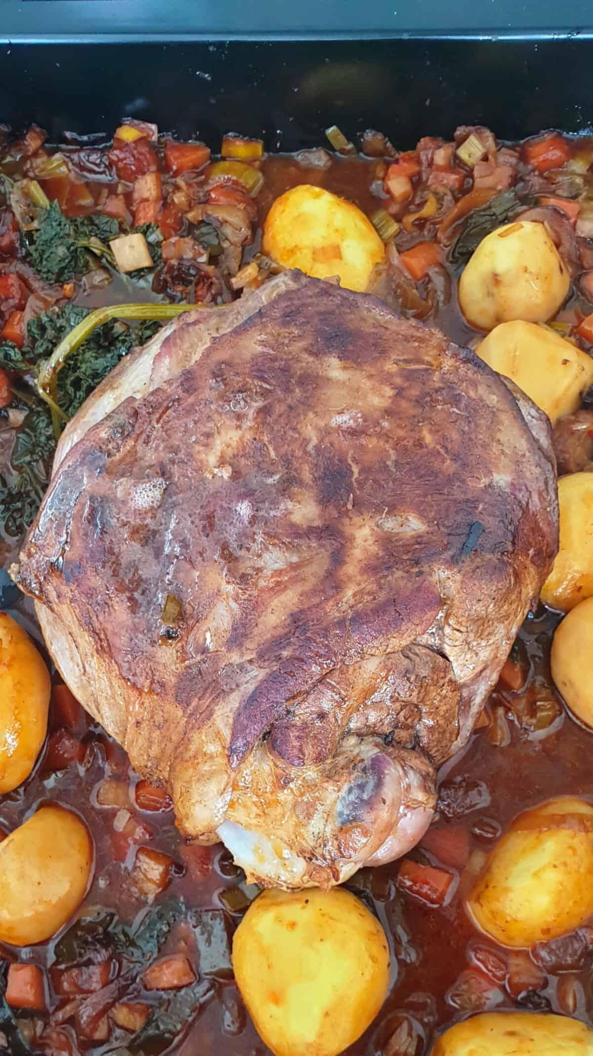 Eine Lammkeule aus dem Backofen mit Kartoffeln in einer Auflaufform.