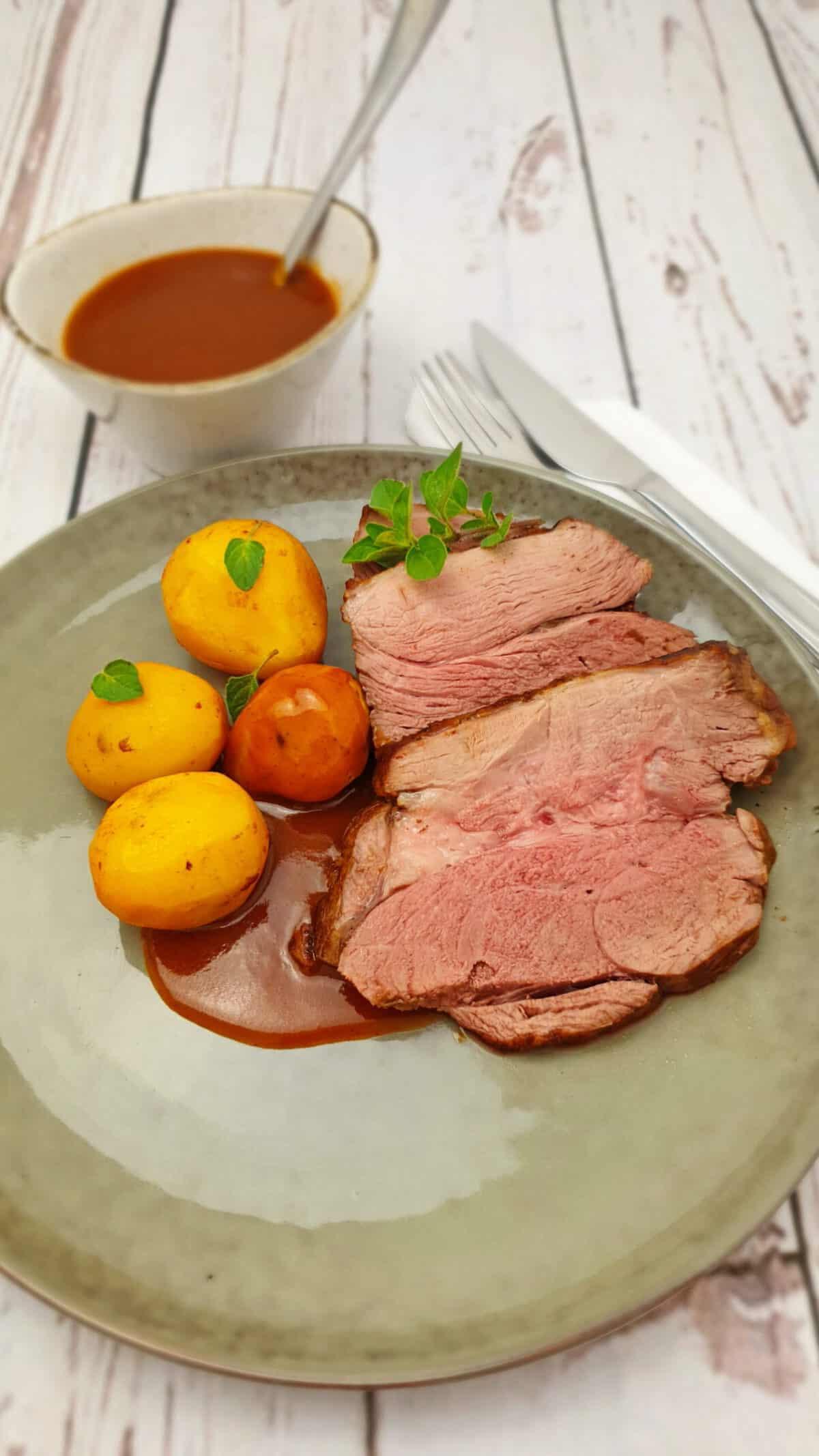 Auf einem grau-grünen Teller angerichtet eine aufgeschnittene Lammkeule mit Kartoffeln und Soße.