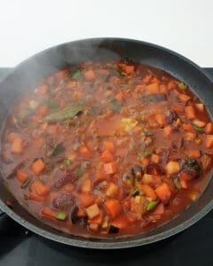 In einer Pfanne angedünstetes Suppengemüse mit Tomatenmark und Brühe.