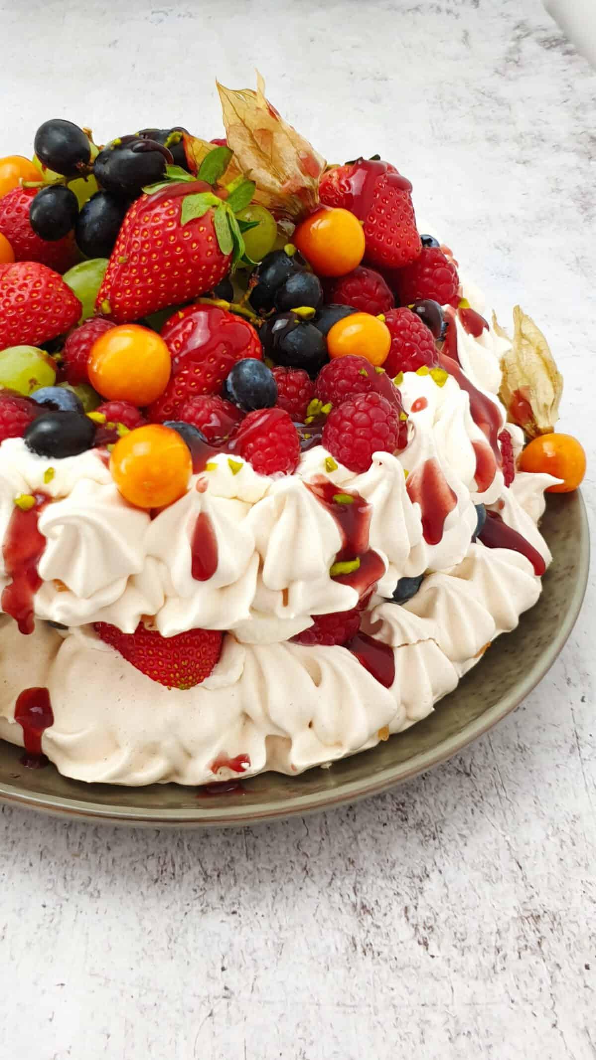 Eine zweischichtige Pavlova Torte mit Sahne Füllung und Früchte Topping auf einem Teller angerichtet.