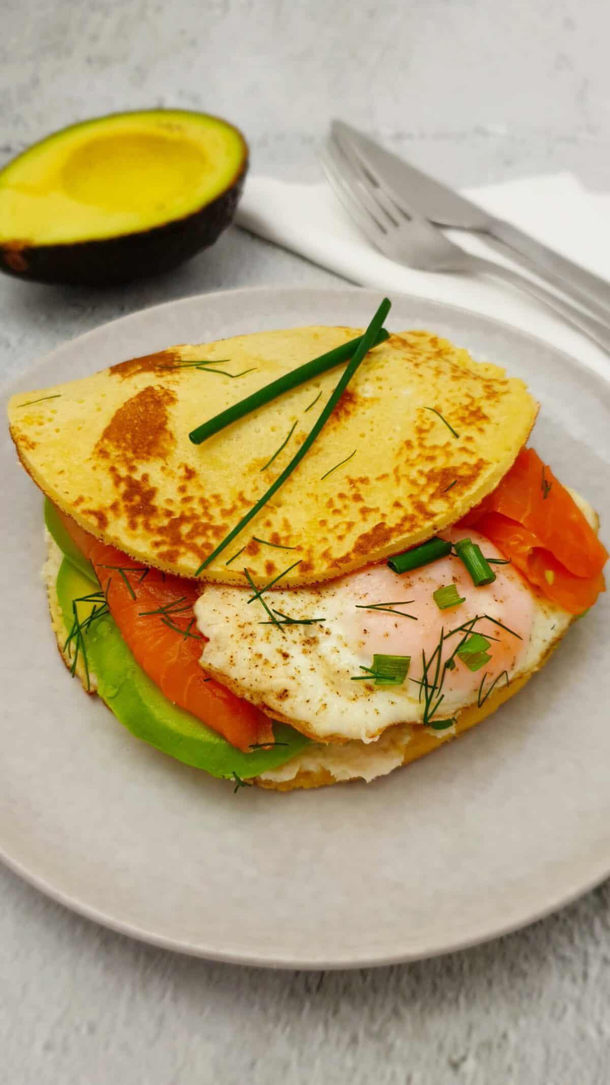 Pfannkuchen Burger - Pancake Burger mit Lachs und Avocado auf einem grauen Teller serviert.