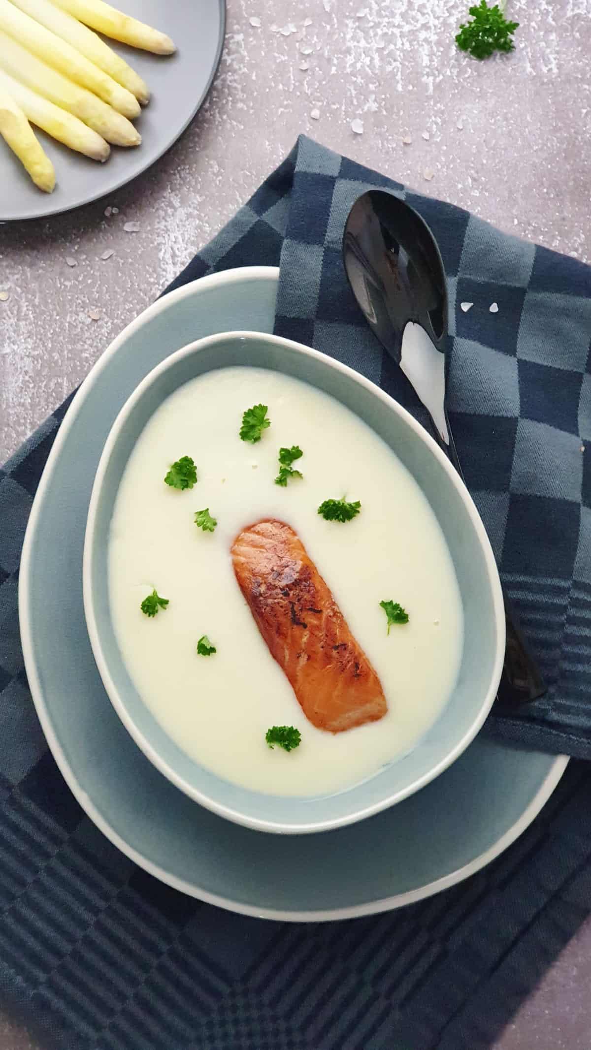 In einer grauen Schale Spargelcremesuppe mit Lachs. Im Hintergrund Deko.