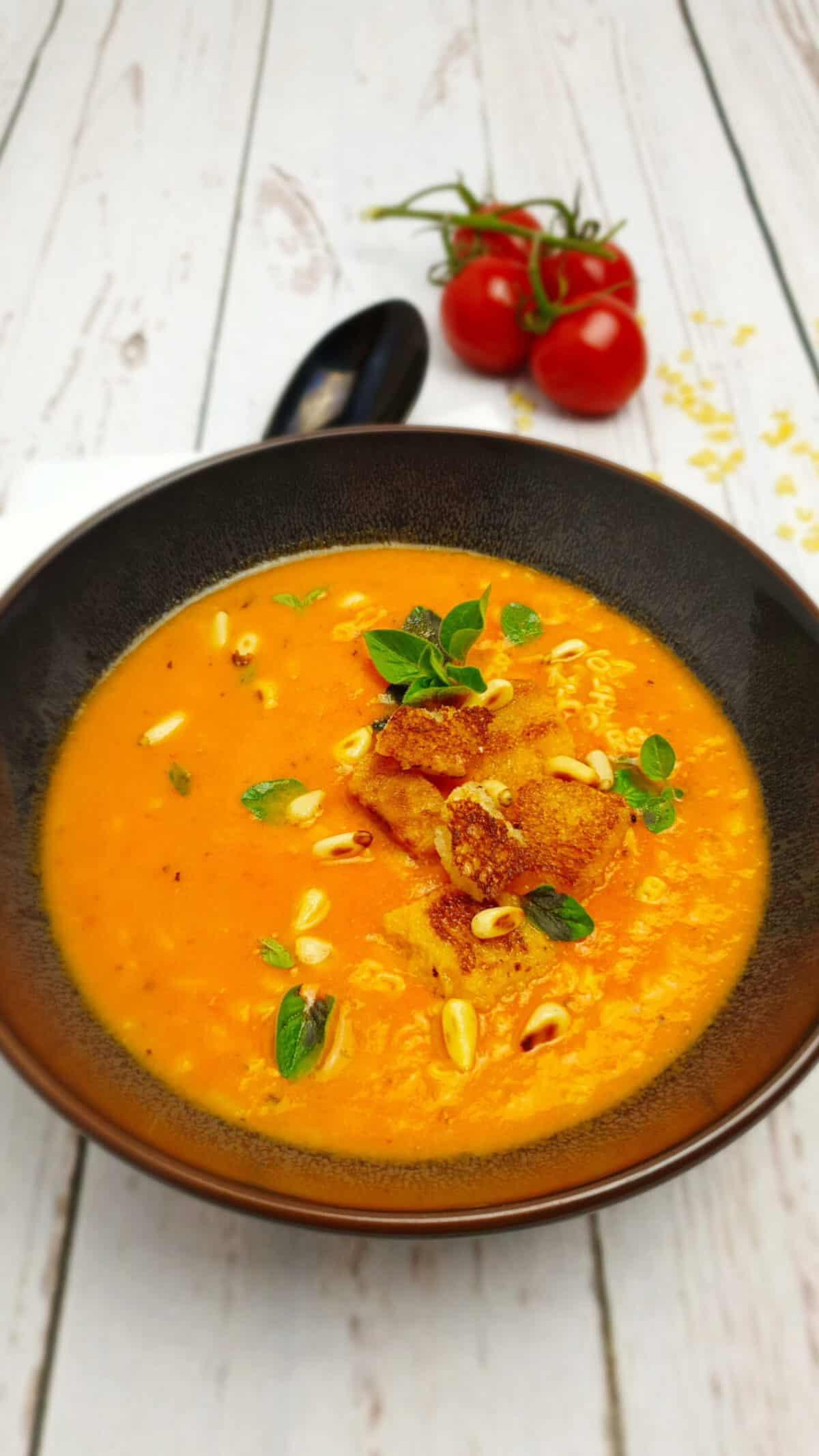 In einer braunen Schale Tomaten-Buchstaben-Suppe mit Croutons und Pinienkernen.