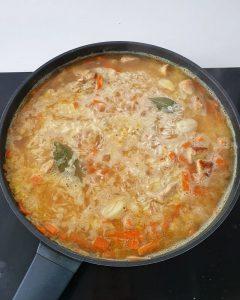 Reis mit Brühe und Gemüse in einer Pfanne.