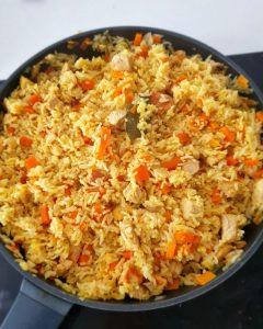 Reis mit Möhren und Pute in einer Pfanne.