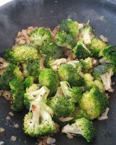 In einer Pfanne angedünsteter Brokkoli mit Zwiebeln.