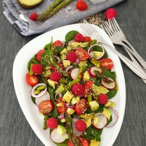 Ein frischer bunter Frühlingssalat mit Avocado und Blattspinat dekorativ angerichtet auf einem weißen Servierteller.
