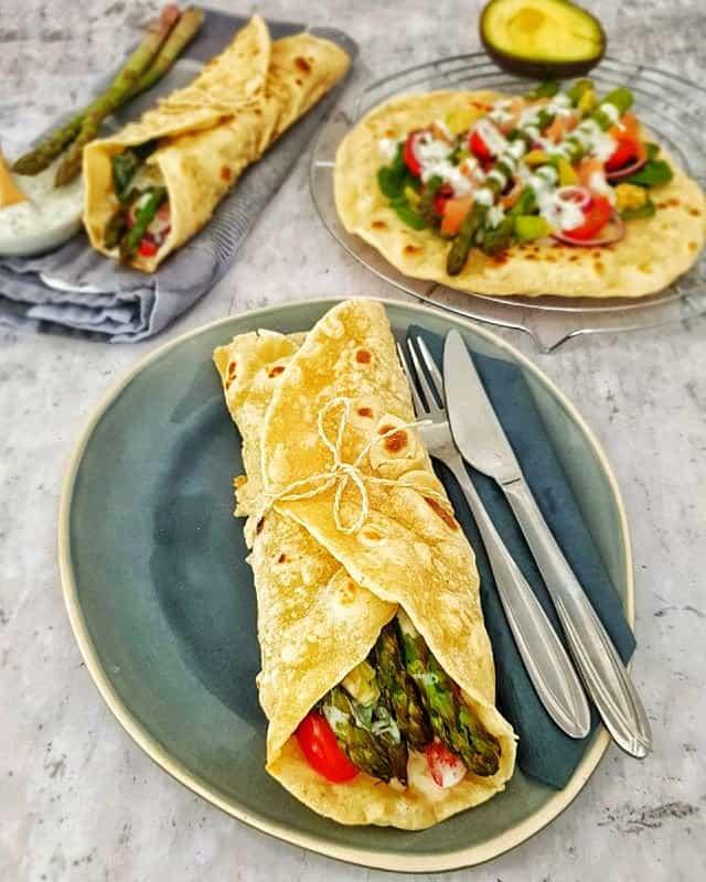 Auf einem ovalen Teller siehst du einen selbstgemachten Dinkel Wraps, gefüllt mit Spargel, Tomate und Avocado.