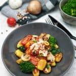Knusprig angeratene Gnocchi auf italienische Art mit Tomatensoße und Parmesan sowie Brokkoli und Spinat. Dekorativ angerichtet in einer grauen Schale. I