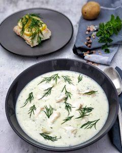 Kartoffelsuppe mit Kräutern und Kabeljau angerichtet in einer dunkelgrauen Schale mit frischem Dill garnieren.