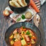 In einer braunen Schale eine Gulasch-Suppe mit Würstchen.