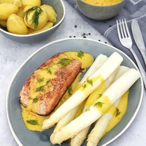 Fünf Spargelstangen mit einem Lachsfilet und Sauce hollandaise angerichtet in dekorativer Art auf einem ovalen Teller. Im Hintergrund eine Schale mit Kartoffeln.