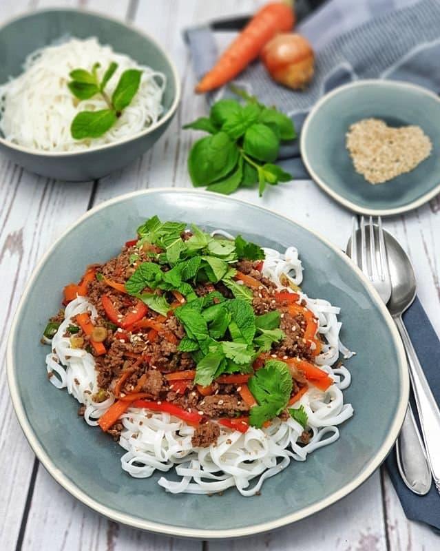 Auf einem ovalen Teller angerichtete Reisnudeln mit Hackfleischsoße und grünen Kräutern. Im Hintergrund eine Schale mit Sesam und eine Schale mit breiten Reisnudeln.