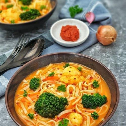 Eine runde Schale mit einer roten Curry-Suppe, Blumenkohl, Brokkoli und Glasnudeln. Dekorativ angerichtet mit Currypaste und Zwiebel sowie Knoblauchzehe im Hintergrund.