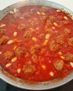 Eine Gußeienpfanne mit einer Tomatensoße und Hackfleischbällchen, die vorher angebraten wurden mit ein paar weißen Bohnen.