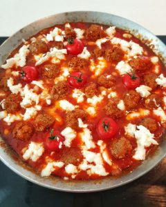In die Pfanne kommt jetzt Mozzarella Käse, der wird auf die Hackbällchen verteilt.