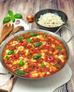 Dekorativ in einer Gußpfanne angerichtete Hackbällchen in Tomaten-Mozzarella Soße mit Basilikum bestreut und einer Schale Reis im Hintergrund.