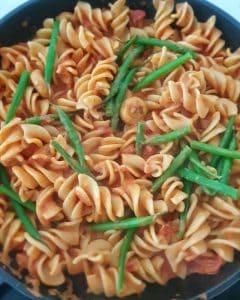 Pasta mit Tomaten-Frischkäse-Soße in einer Pfanne mit grünen Bohnen.
