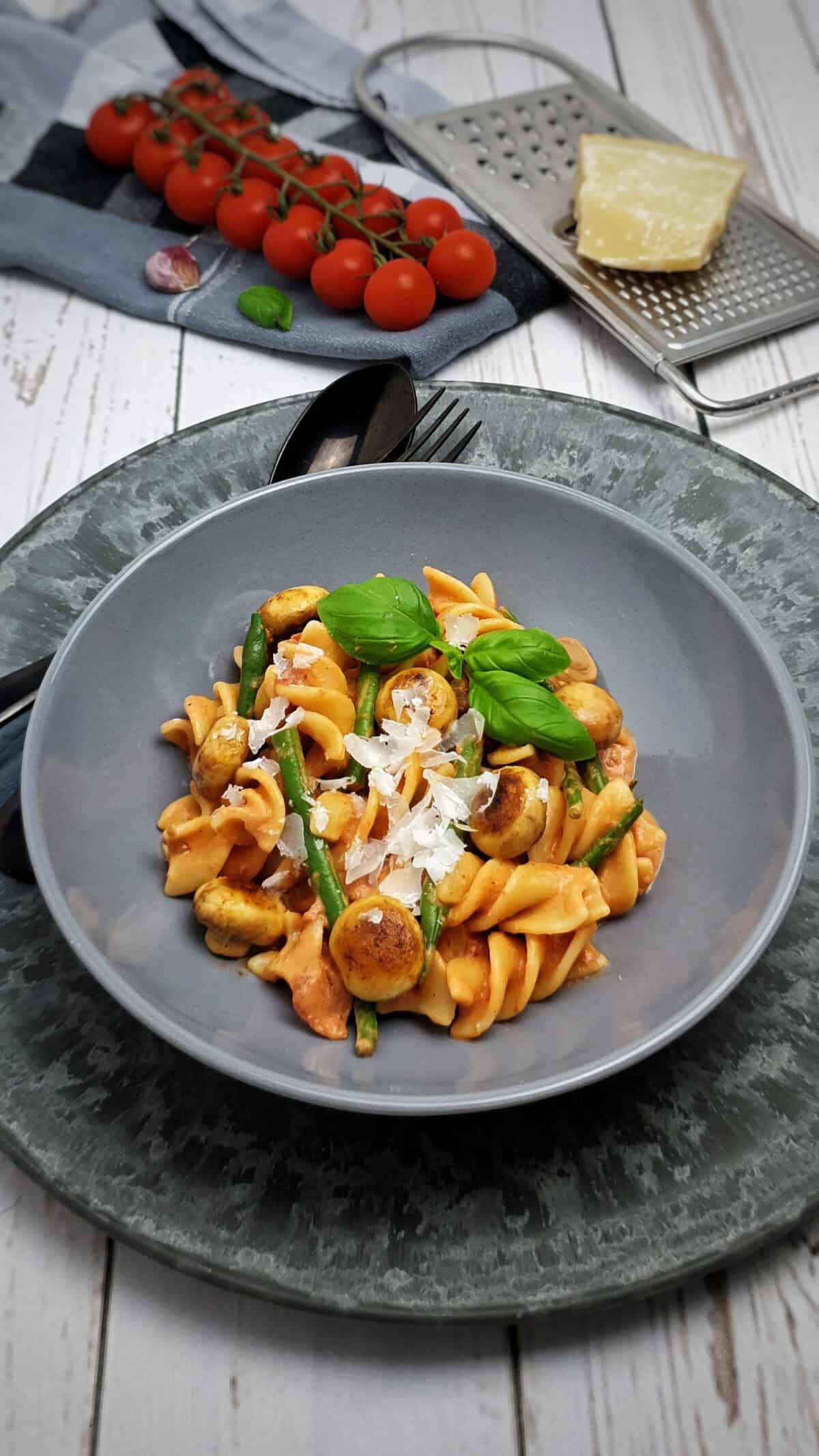 Pasta mit Tomaten-Frischkäse-Soße in einer grauen Schale angerichtet. Mit Parmesan bestreut und mit Basilikum serviert.
