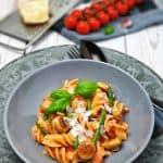 In einer grauen Schale dekorativ angerichtete Pasta mit Tomaten-Frischkäse-Soße mit Mini Champignons und grünen Bohnen. Serviert mit Parmesan und Basilikum. Im Hintergrund Deko.