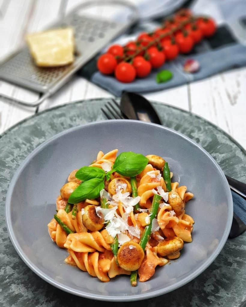 In einer grauen Schale dekorativ angerichtete Tomaten Nudeln mit Mini Champignons und grünen Bohnen