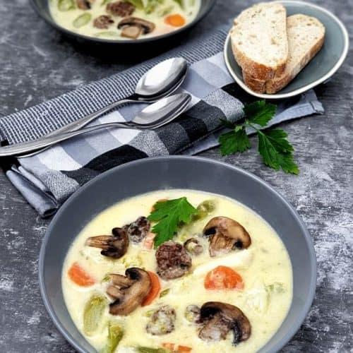 Eine weiße Spargelsuppe in einer grauen Schale angerichtet mit Hackbällchen, Möhren und Champignons als Einlage.