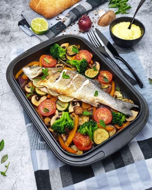 In einer dunklen Auflaufform abgebildet liegt ein ganzer Wolfsbarsch auf buntem Ofengemüse. Der Fisch ist gebacken und knusprig. Im Hintergrund zu sehen ist ein Baguette und eine Schale mit selbstgemachtem Aioli.