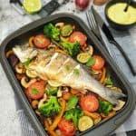 Ein ganzer Fisch auf einem Gemüsebett in einer Auflaufform dekorativ angerichtet. Zu sehen sind Tomaten, Zucchini, Paprika und ein Wolfsbarsch.