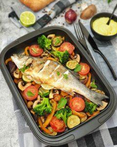 Ein ganzer Fisch auf einem Gemüsebett in einer Auflaufform dekorativ angerichtet. Zu sehen sind Tomaten, Zucchini, Paprika und ein Wolfsbarsch