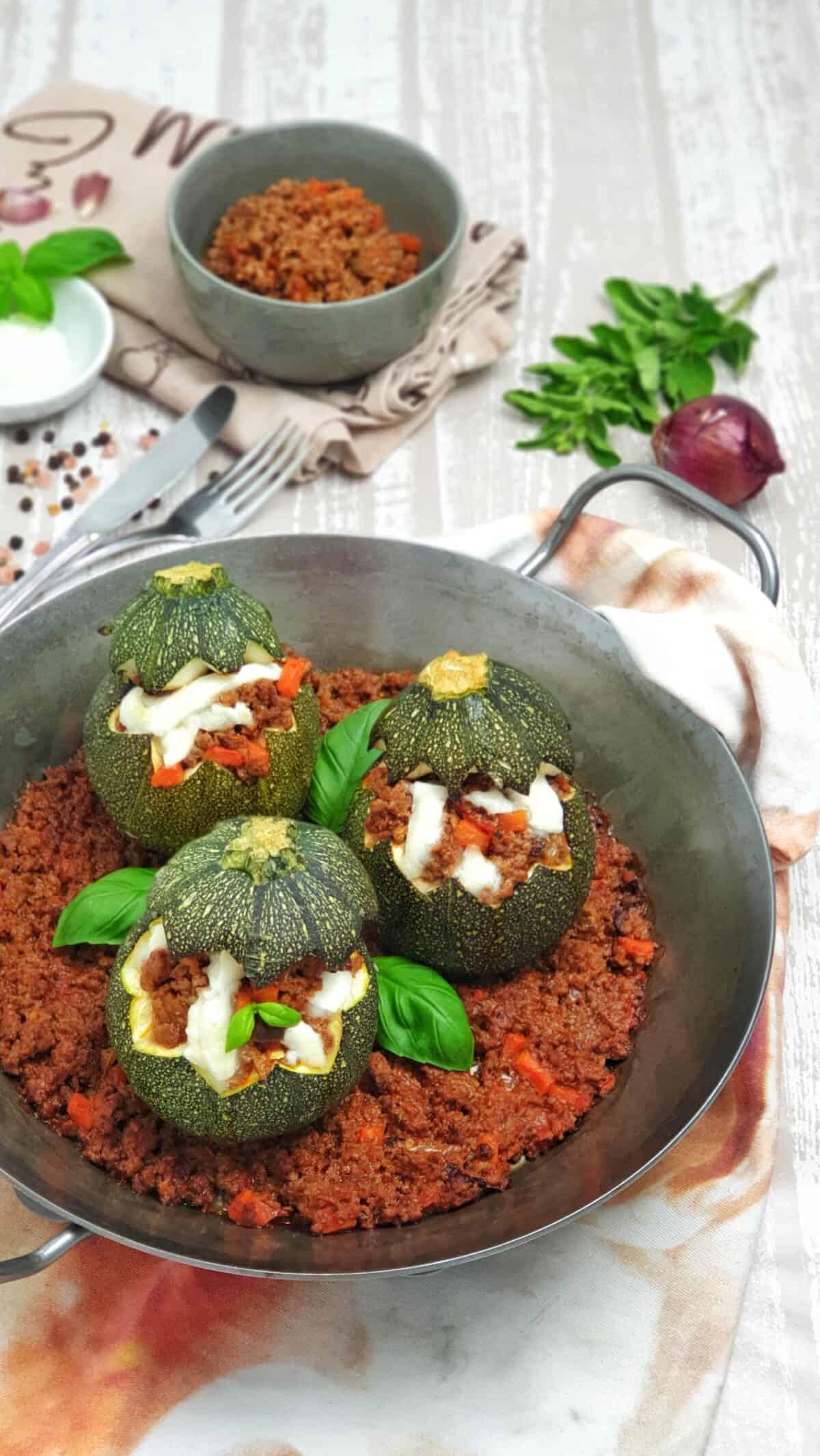 Gebackene Zucchini mit Hackfleisch-Tomatensoße aus dem Ofen. Mit Käse überbacken in einer Gußpfanne serviert.
