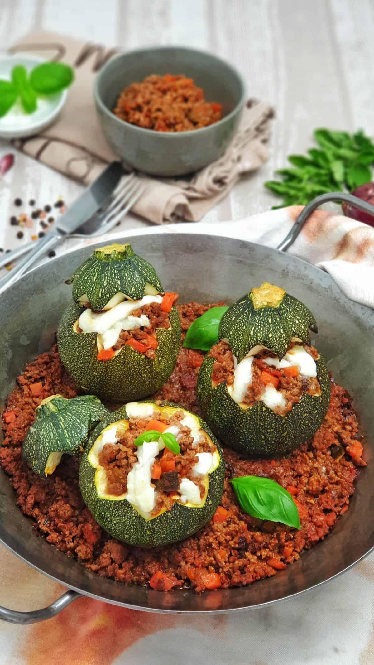 Gefüllte Zucchini mit Hackfleisch-Tomatensoße aus dem Ofen. Mit Käse überbacken in einer Gußpfanne serviert.