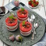 Joghurt-Schicht-Dessert mit Erdbeerpüree im Glas. Dekoriert mit Schokostreusel, gehackten Pistazien und frischen Minzblättern.
