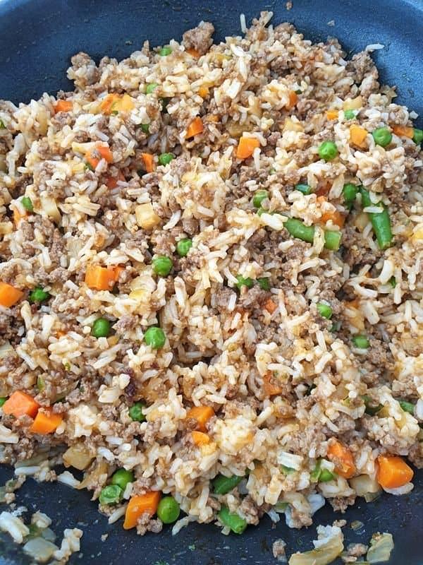 In einer Pfanne Reis mit Hackfleisch und Gemüse.