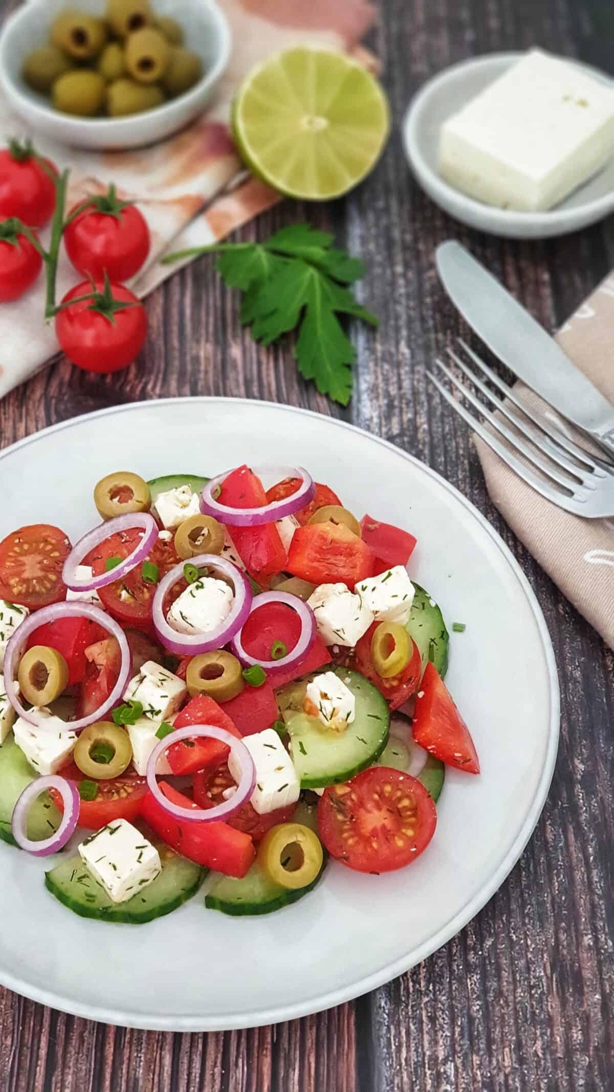 Auf einem hellen Teller angerichtet ein Bauernsalat mit Feta. Im Hintergrund Deko.