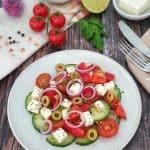 Auf einem hellen Teller angerichteter griechischer Bauernsalat mit Tomaten, Gurken, roten Zwiebeln und Feta.