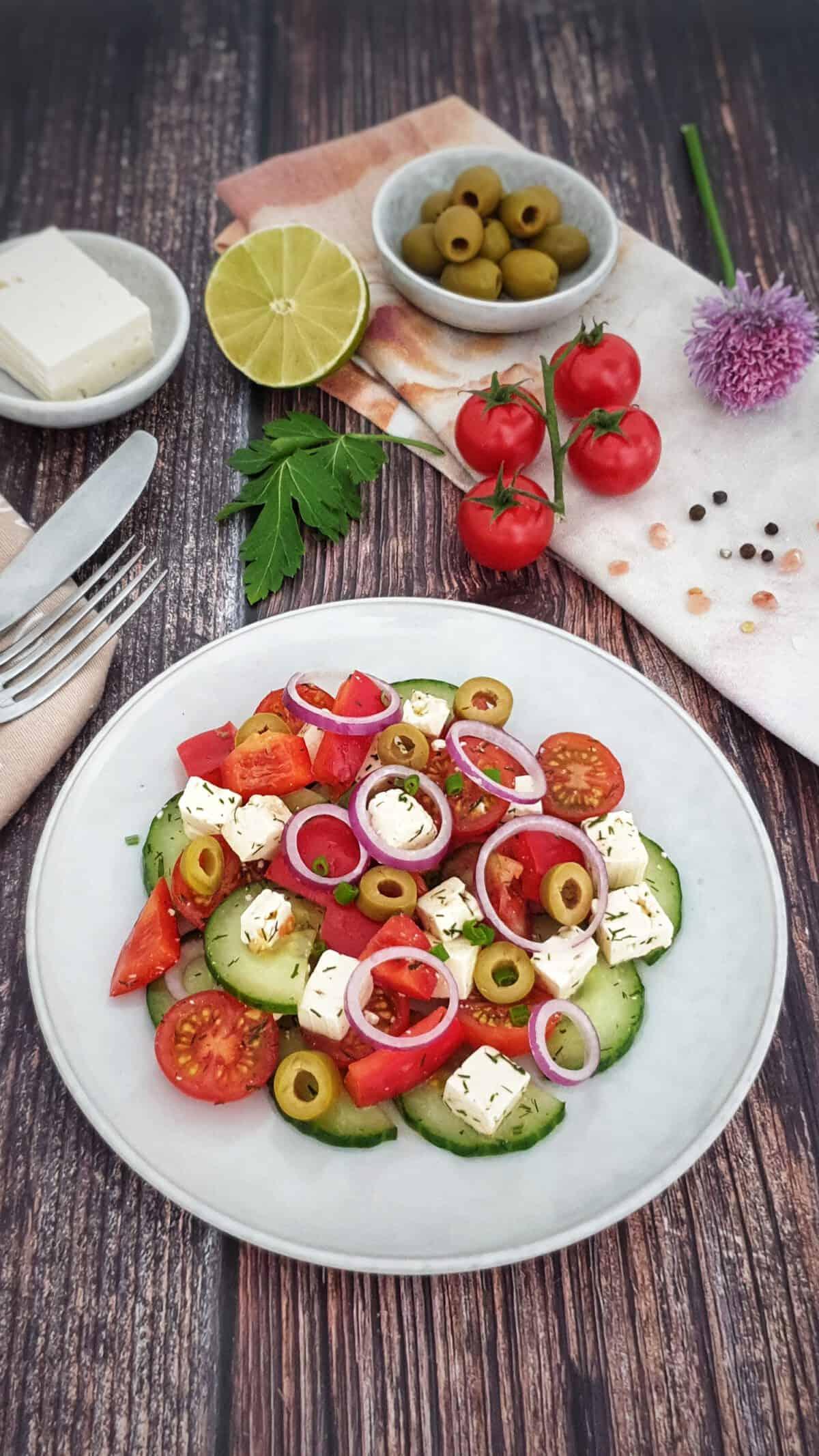 Auf einem hellen Teller angerichtet ein griechischer Bauernsalat mit Feta. Im Hintergrund Deko.