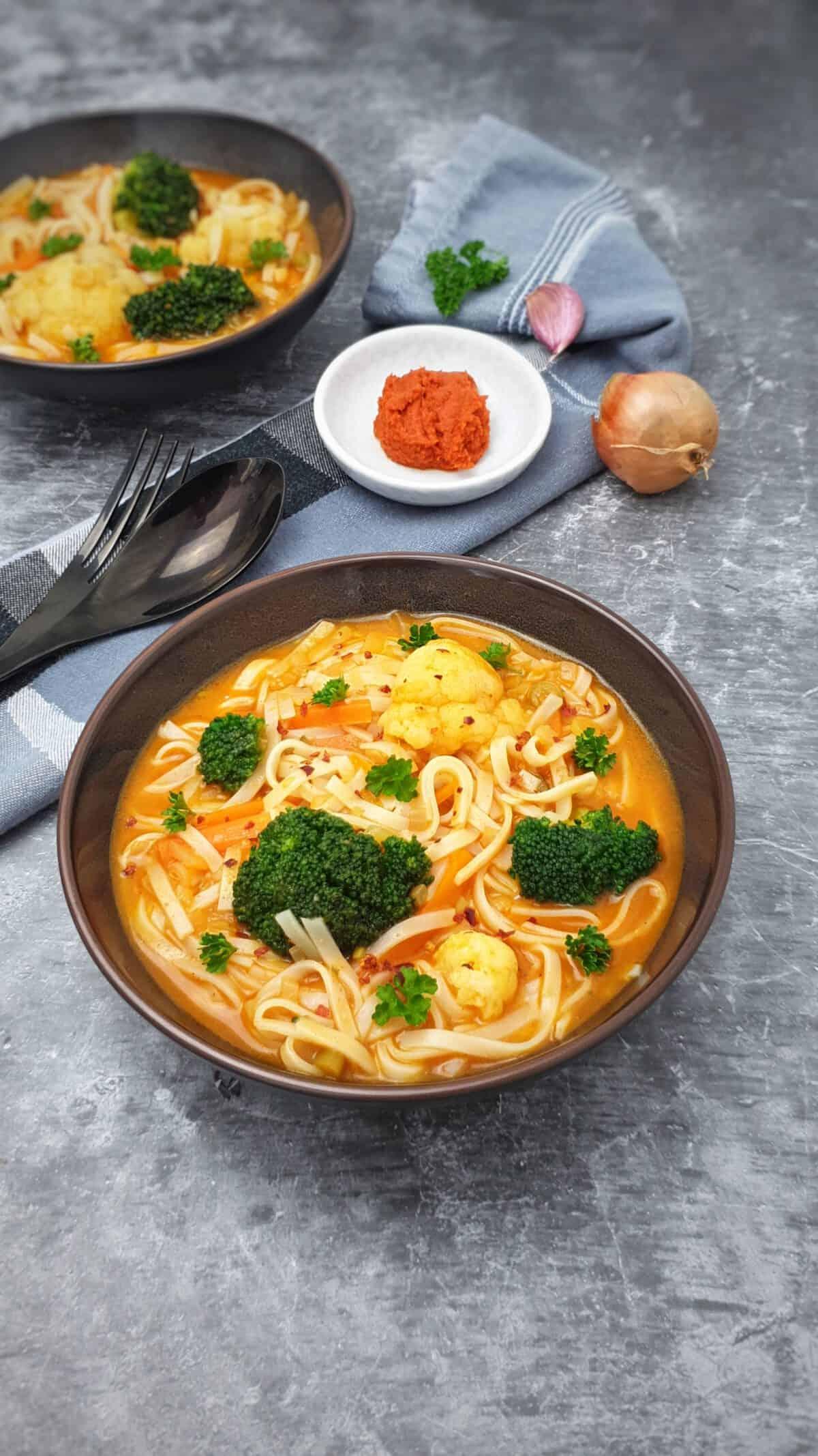 In einer braunen Schale eine rote Currysuppe mit Glasnudeln, Brokkoli und Blumenkohl. Im Hintergrund Deko.