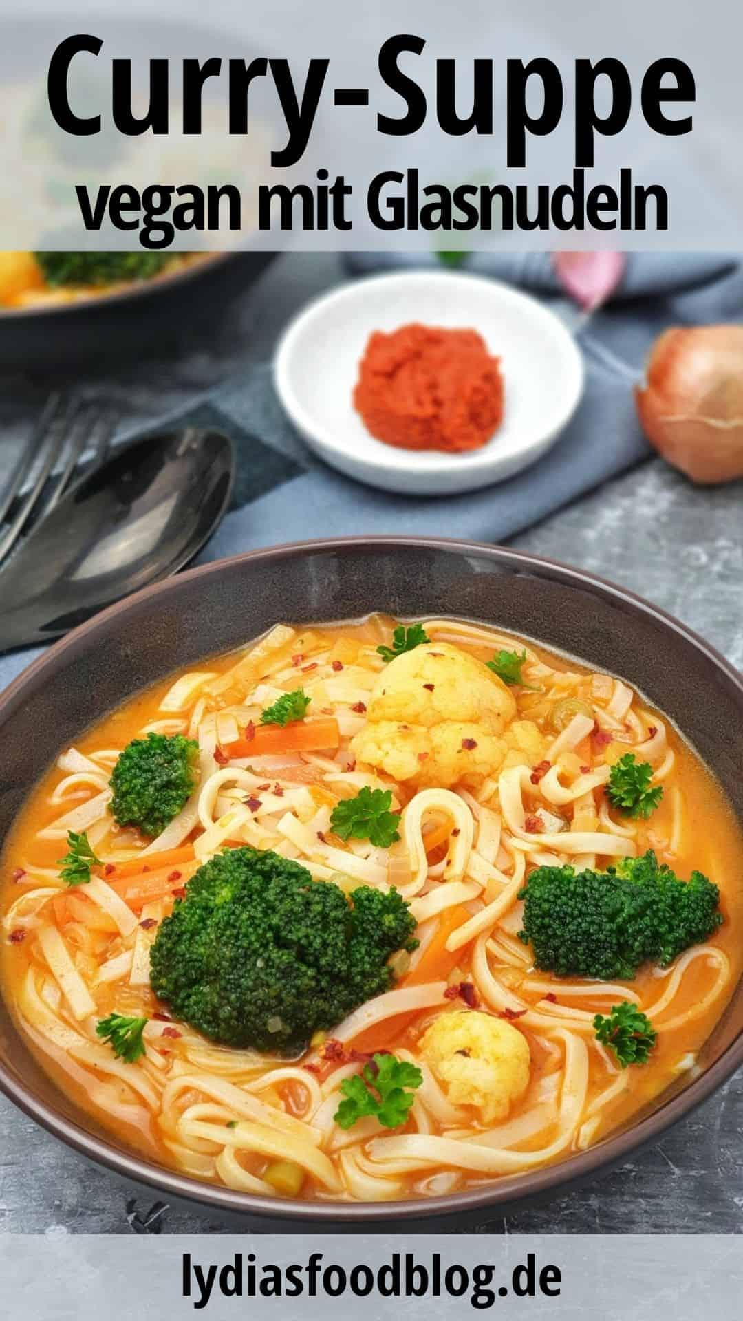 In einer braunen Schale eine rote Curry-Suppe mit Glasnudeln, Brokkoli und Blumenkohl. Im Hintergrund Deko.