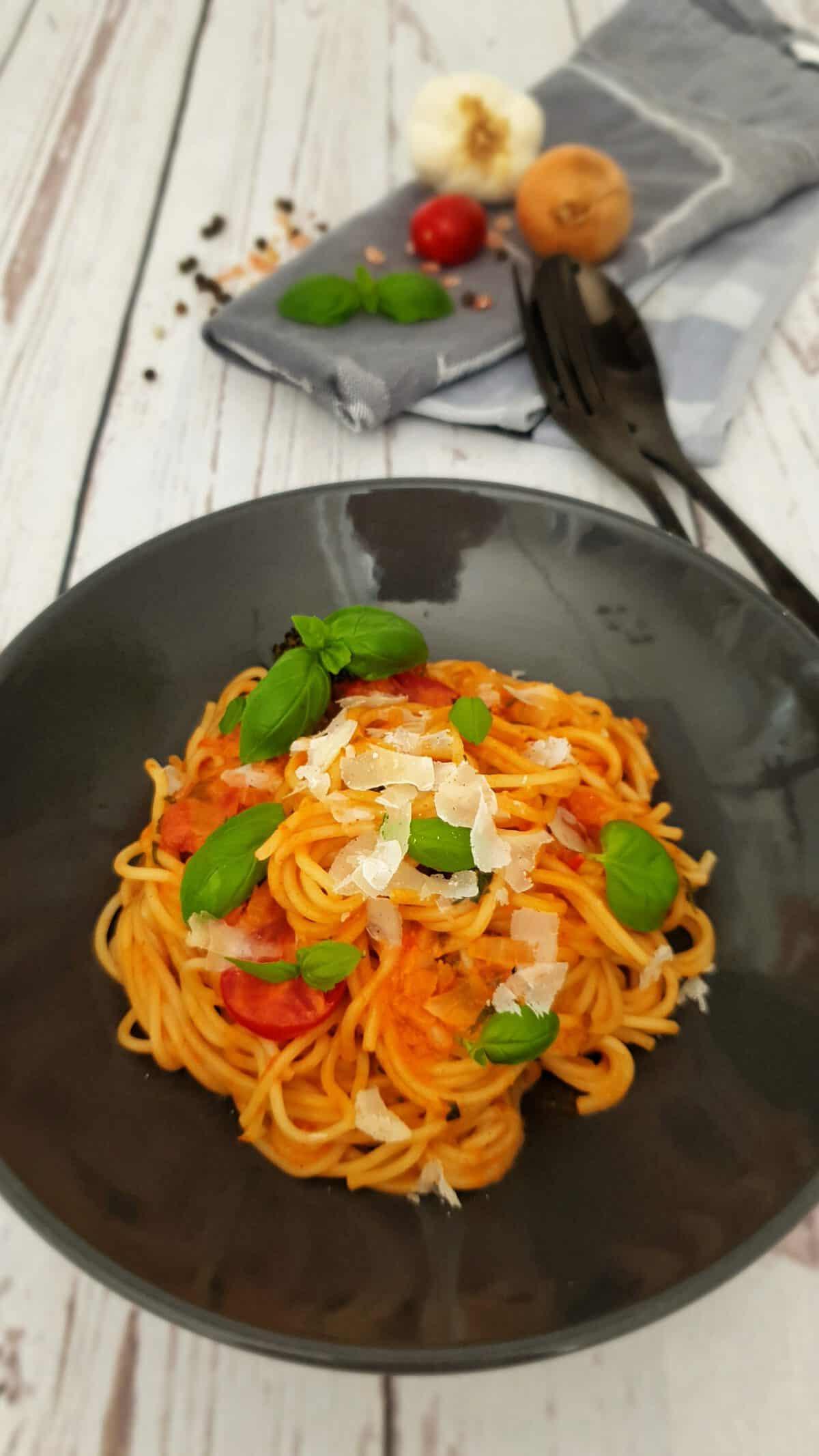 In einer braunen Schale angerichtet Dinkel Spaghetti mit Tomaten-Kokosmilch-Soße. Garniert mit Basilikum Blättern.