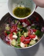 In einer Schale ein gemischter bunter Salat und eine Schale mit Dressing.