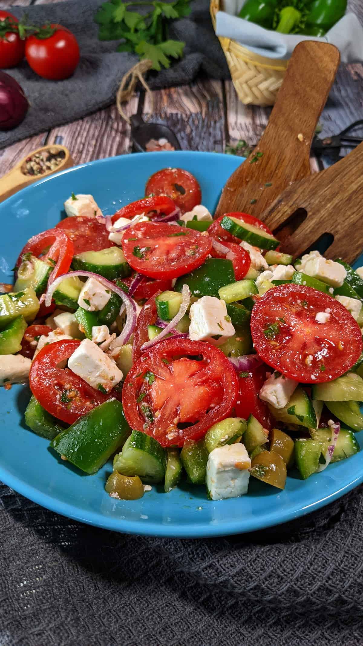 In einer blauen Schale ein bunter Griechischer Bauernsalat mit Feta. Im Hintergrund Deko,