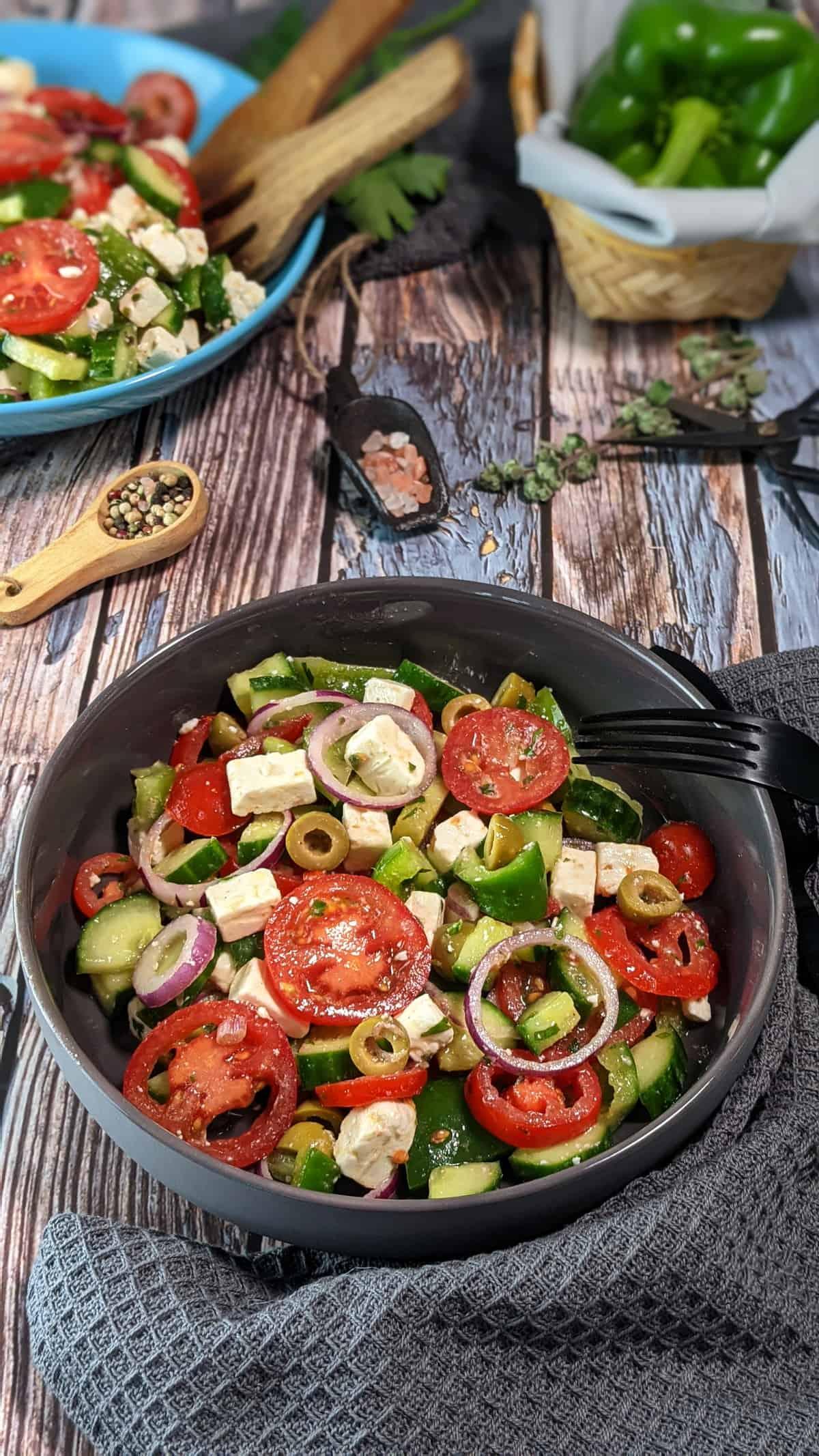 In einer grauen Schale angerichtet ein griechischer Bauernsalat mit Fetakäse. Im Hintergrund Deko.