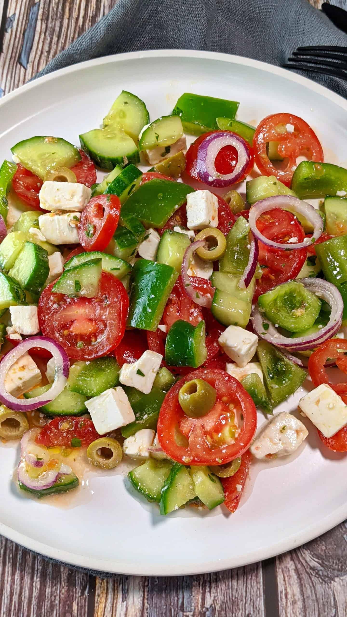 Auf einem weißen Teller angerichtet ein bunter Bauernsalat mit Fetakäse. Im Hintergrund Deko.