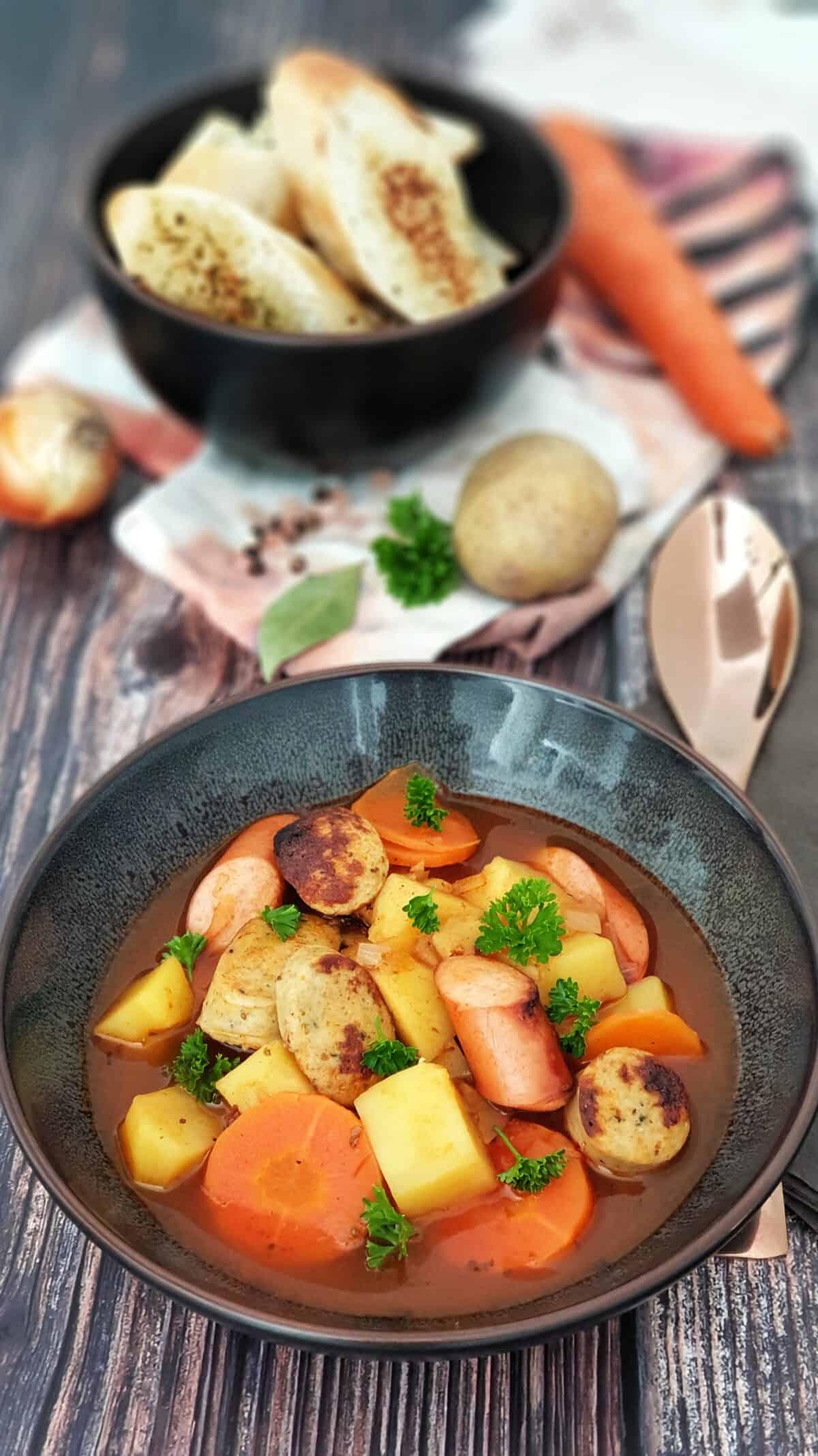 In einer braunen Schale eine Gulasch-Suppe mit Würstchen. Im Hintergrund Deko.