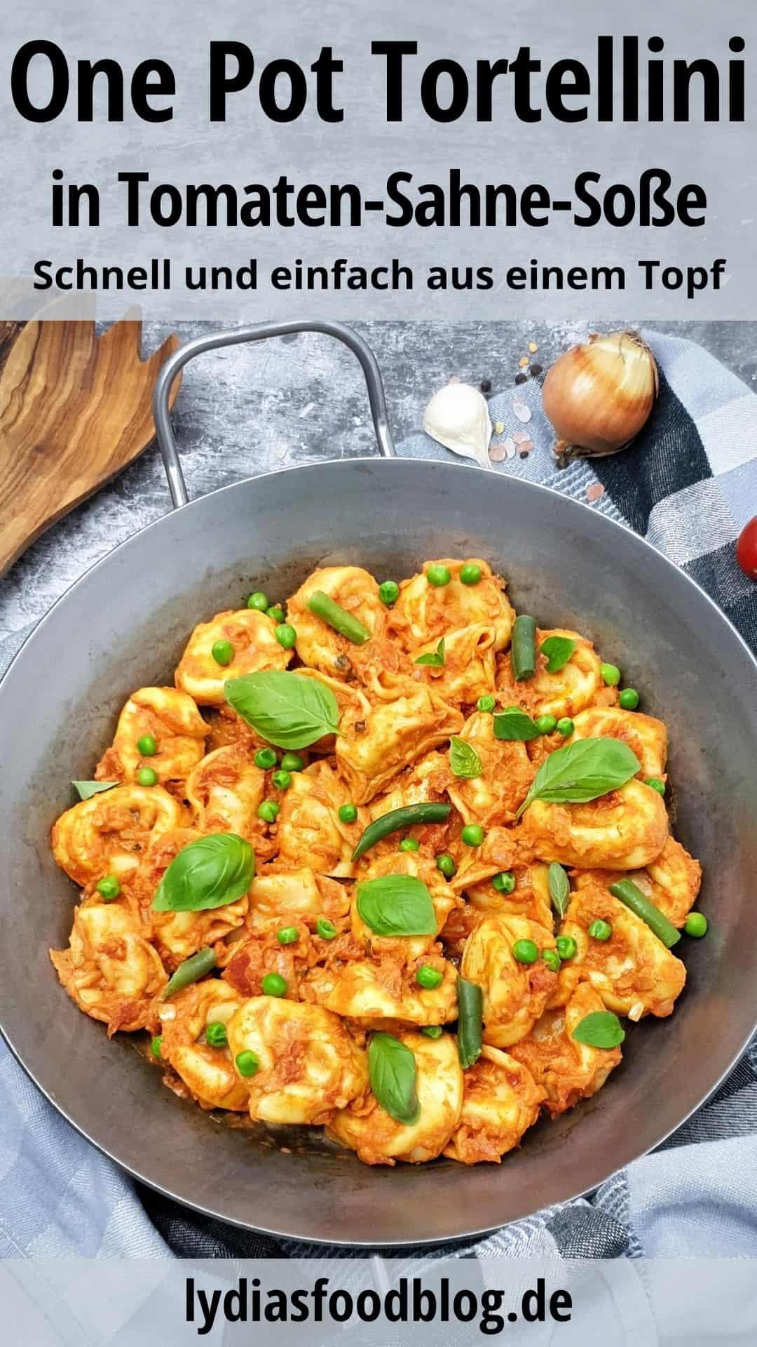 In einer gußeisernen Pfanne angerichtet One Pot Tortellini in Tomaten-Sahne-Soße mit Basilikum garniert. Im Hintergrund Deko.